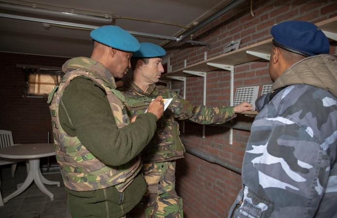 Yassin Musa en zijn kompaan Ronald controleren de 'wapenopslagplaats'. Rechts de 'commandant' van de opslagplaats Hassen Nur Ahmed.