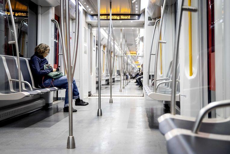 Reizigers in de metro in Amsterdam. Het  openbare stadsvervoer gaat weer meer rijden nu kinderen en jongeren meer bewegingsvrijheid krijgen in de maatregelen rondom het coronavirus.  Beeld ANP