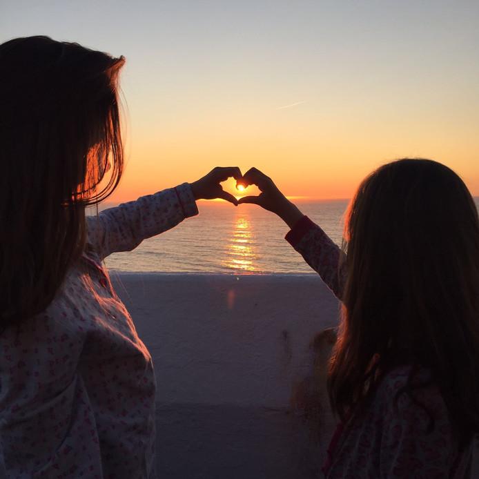 De kleindochters van Kees Looije uit Hendrik-Ido-Ambacht vangen de zon in een hartje, als deze onder gaat aan de Noorse kust.