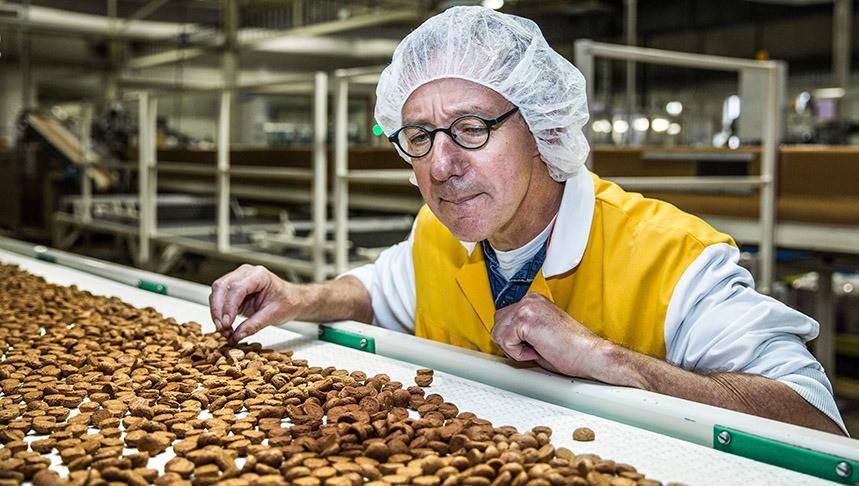 Medewerker Jan Bloemena van bakker Van Delft bij de lopende band vol kruidnootjes
