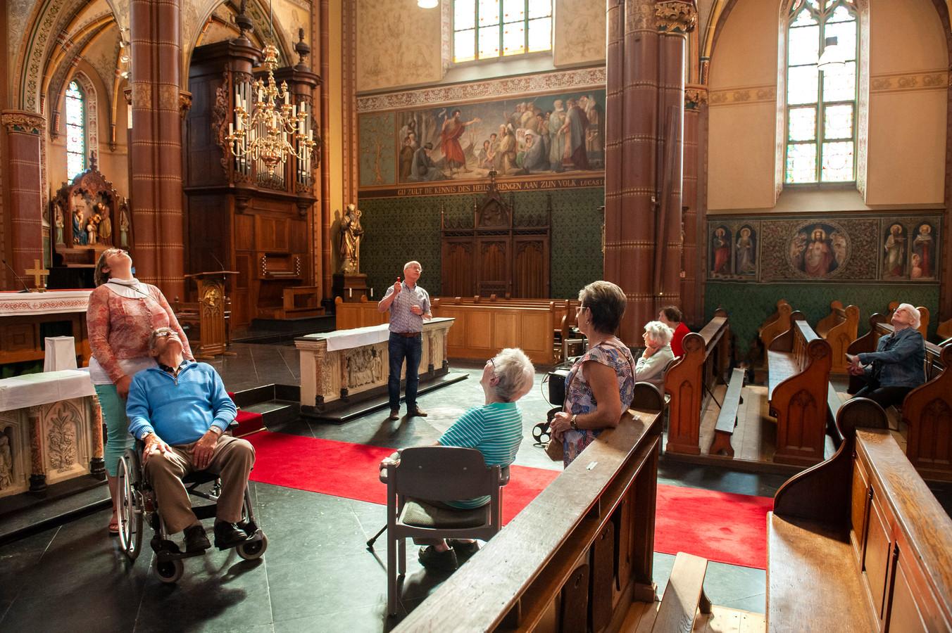 Koos van de Loo (l) en daarachter Esther Schellekens luisteren naar Jan Verstijnen in de Nicolaaskerk in Helvoirt.