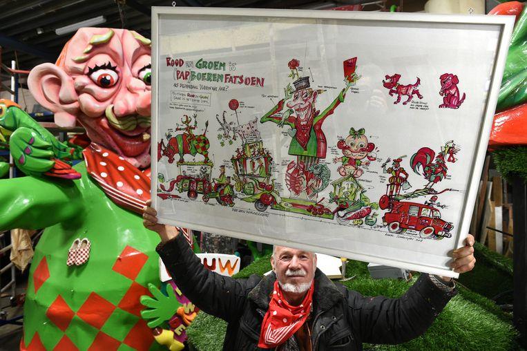 Karel Schrooyen met zijn ontwerp voor de praalwagen van Wouw dit jaar. Op de achtergrond wordt de wagen gebouwd. Beeld Marcel van den Bergh