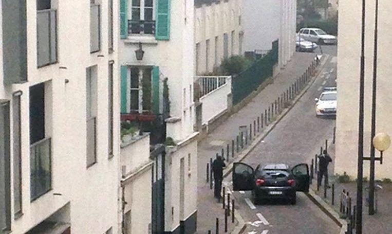 Gewapende mannen staan oog in oog met een politieauto nabij de redactie van Charlie Hebdo. Beeld afp