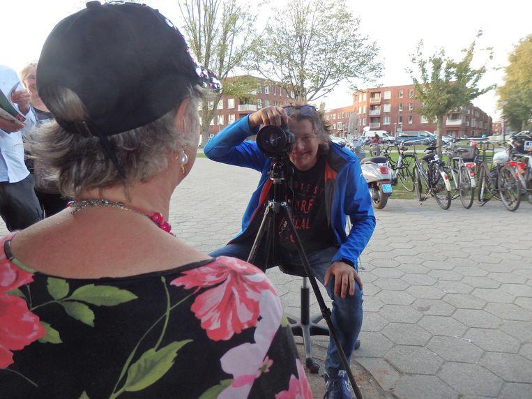 Fotograaf Ruben Timman maakt live portretten van de bezoekers. 'Kijk door die camera heen!' Beeld Hans van der Beek