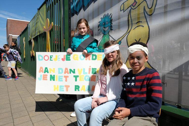 Leerlingen Emma en Liam hebben voor de actie een verband rond hun hoofd aangebracht.