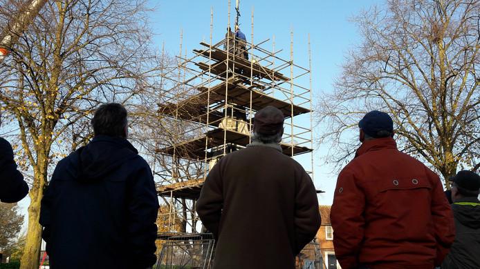 Een aantal vrijwilligers kijkt toe hoe de vrijwilligers zonder hoogtevrees de haan op het torentje terugplaatsen.