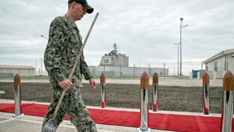 Een soldaat maakt vlak voor de opening van een NAVO-basis in Roemenië de rode loper schoon.