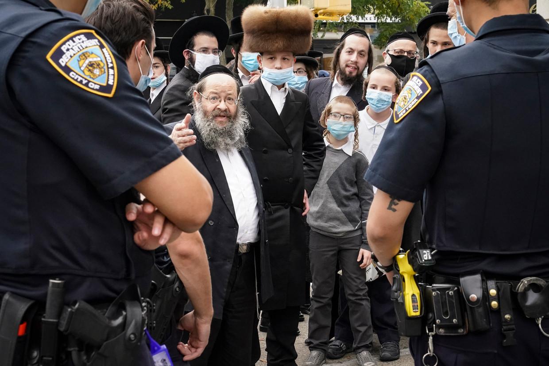 Leden van de joods-orthodoxe gemeenschap in de New Yorkse wijk Borough Park in gesprek met de politie. Beeld AP