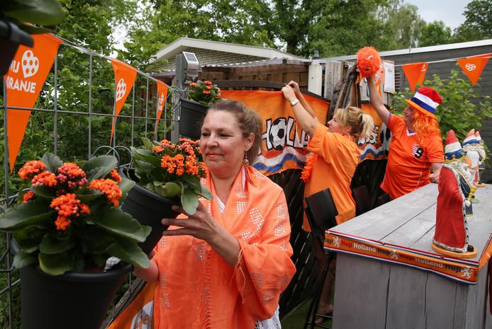 De tuin van Coby Hoekstra (voorgrond) kleurt helemaal oranje. Alles wordt gereed gemaakt voor de aftrap van het wk-voetbal voor vrouwen. Miranda en Silvano helpen mee met versieren.