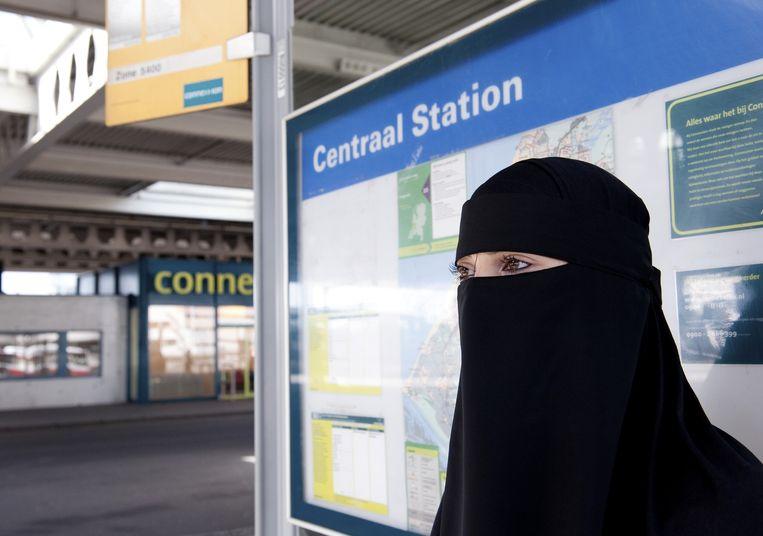 Vrouw met een nikab bij een bushalte. Beeld ANP
