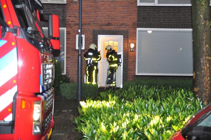 Brandweerlieden met zuurstofmaskers gaan de woning binnen.