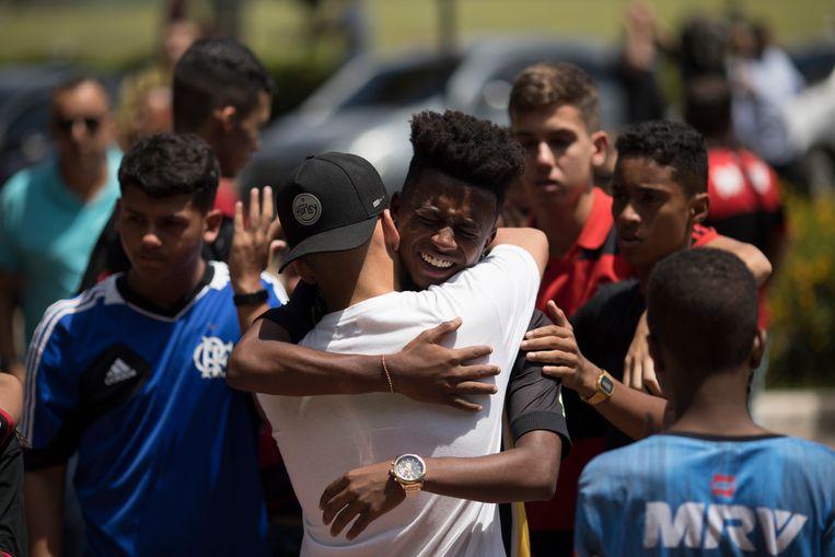 Vrienden van een van de omgekomen spelers troosten elkaar.
