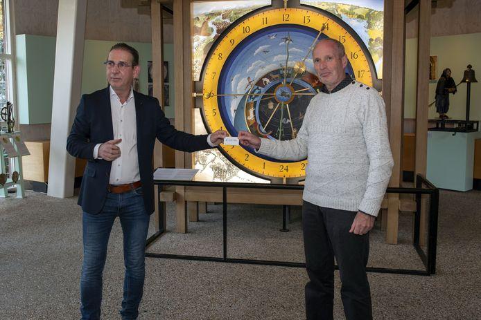 Joop van Dijck van Leergeld Asten-Someren (l) krijgt van museum-medewerker Bram Nugteren het eerste pasje uitgereikt.