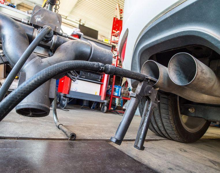 Een apparaat waarmee de CO2-uitstoot kan worden getest is bevestigd aan de uitlaat van een Volkswagen Golf Beeld anp