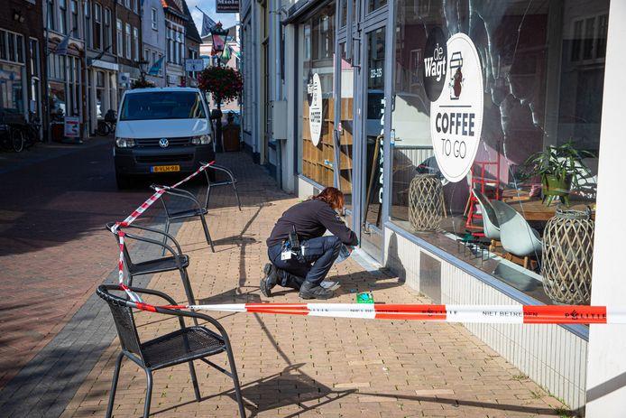 Een medewerker van de Forensische Opsporing verzamelt sporen en bewijsstukken bij de koffiezaak aan de Oudestraat.