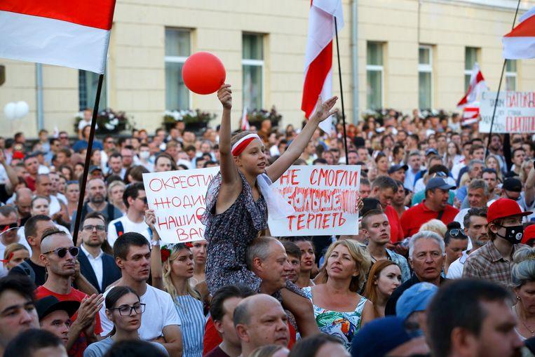 Een meisje is boven een menigte getild die zich heeft verzameld bij een detentiecentrum tijdens een demonstratie, afgelopen maandag. Beeld AP