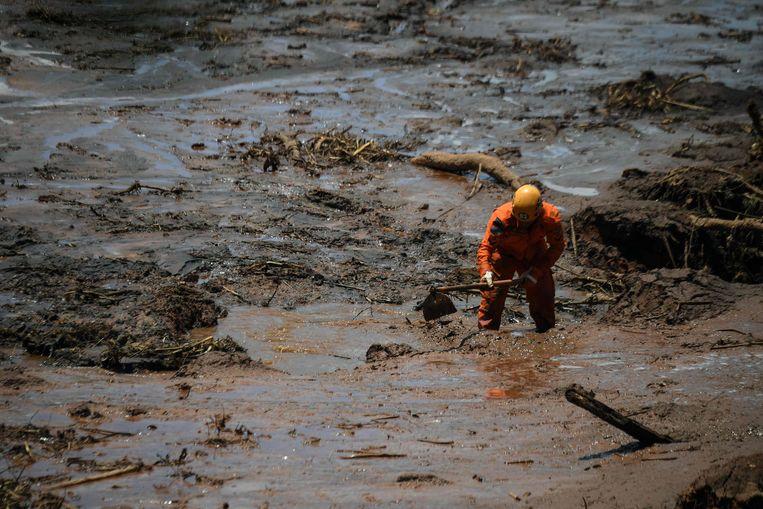 Een reddingswerker zoekt vier dagen nadat de dam bij een ijzerertsmijn van het bedrijf Vale doorbrak, naar slachtoffers vlakbij Brumandinho. Beeld AFP, Mauro Pimentel