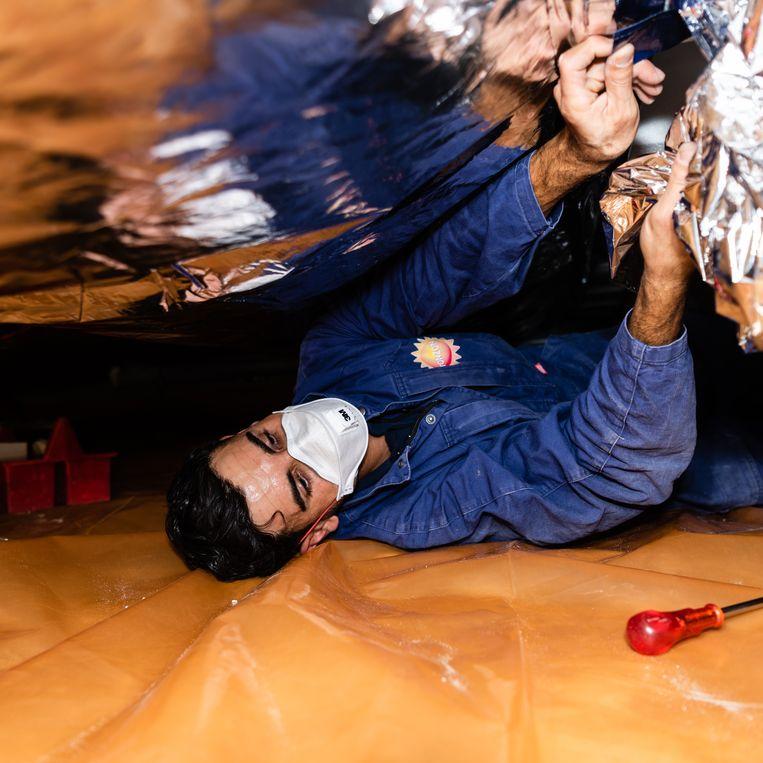 Een werknemer van Tonzon brengt isolatiemateriaal aan in een kruipruimte. Beeld Katja Poelwijk