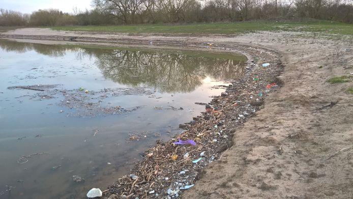 Afval langs de oever bij het Over de Maas-project.