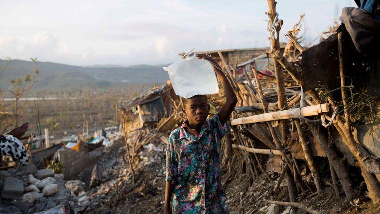 Een kind draagt een container met water voorbij enkele huizen die volledig verwoest werden door orkaan Matthew in Jeremie, Haïti.
