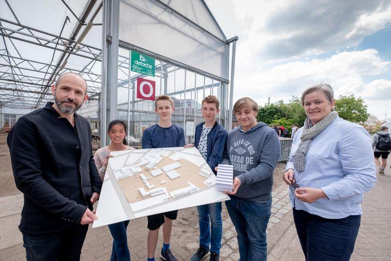 De leerlingen en de architect tonen de bouwplannen.