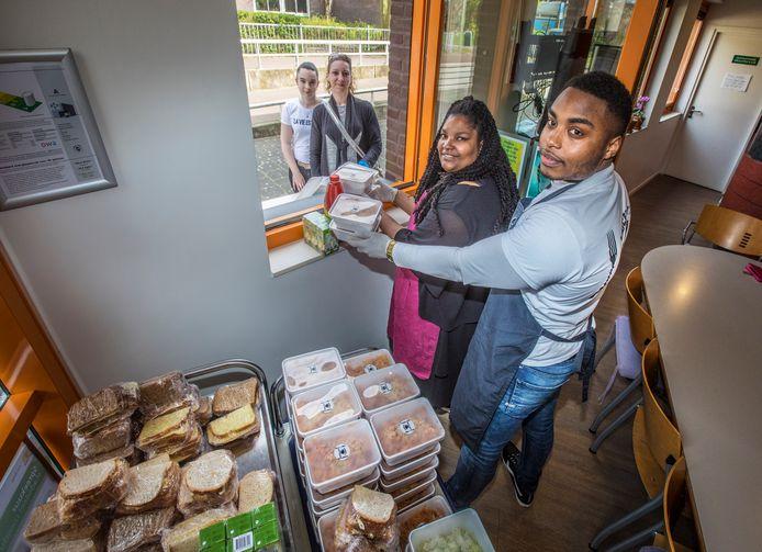 Familie Baumgard deelt maaltijden uitvan uit buurthuis De Geest aan de Georges Bizeststraat. Op de foto moeder Samantha en zoon Laicerey Baumgard die maaltijden meegeven aan Debora en Desteny. (Den Haag 06-04-20) Foto: Frank Jansen