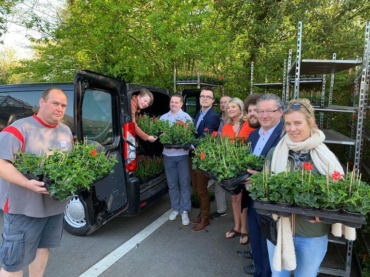 Burgemeester Dirk De fauw en schepenen Mathijs Goderis en Mercedes Van Volcem helpen de bloemen uitdelen.