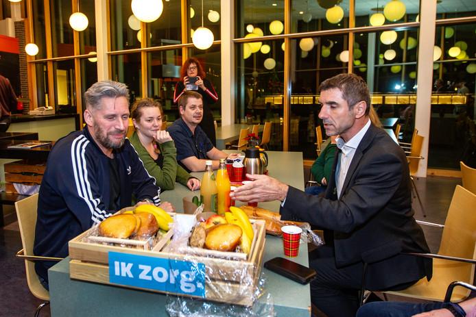 Paul Blokhuis (rechts) verwent medewerkers van Dimence met gezonde voeding tijdens een werkbezoek.