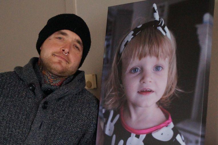 Tim D'heedene bij een foto van zijn overleden dochtertje Nyah.