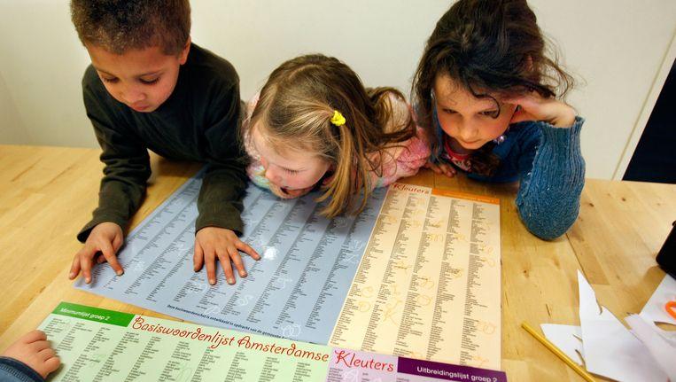 Kinderen buigen zich over een basiswoordenlijst. Beeld anp