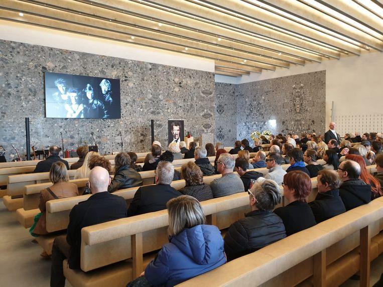 Een foto van Willy Willy met de andere leden van The Scabs vooraan in de aula van het crematorium in Aalst waar mensen woensdag afscheid nemen van de bekende muzikant.