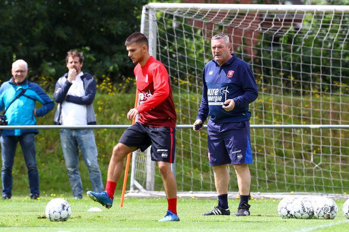 FC Twente-trainer Ron Jans kijkt hoe Lindon Selahi een bal onder controle brengt.