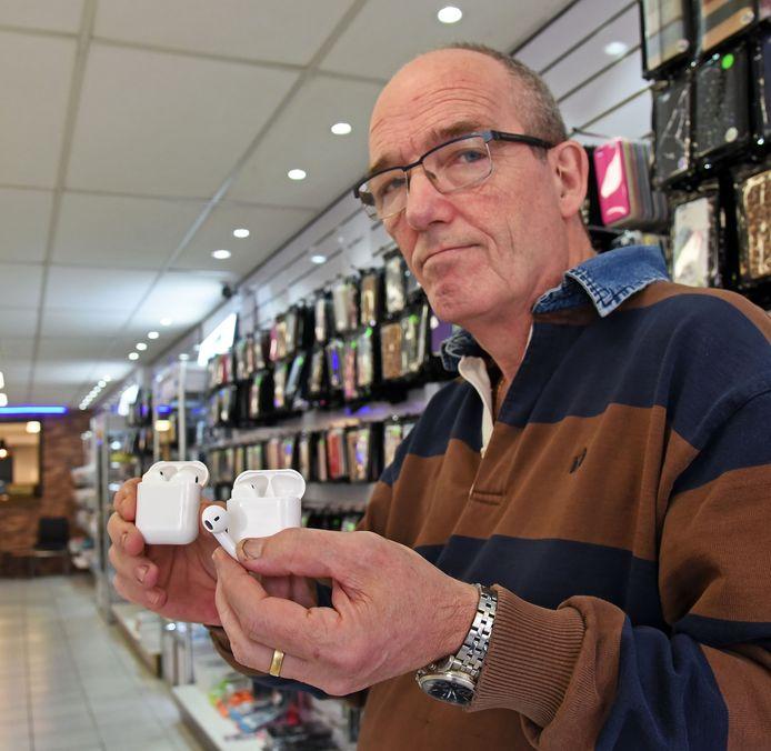 Kees van Sante in zijn belwinkel, met de namaak AirPods.