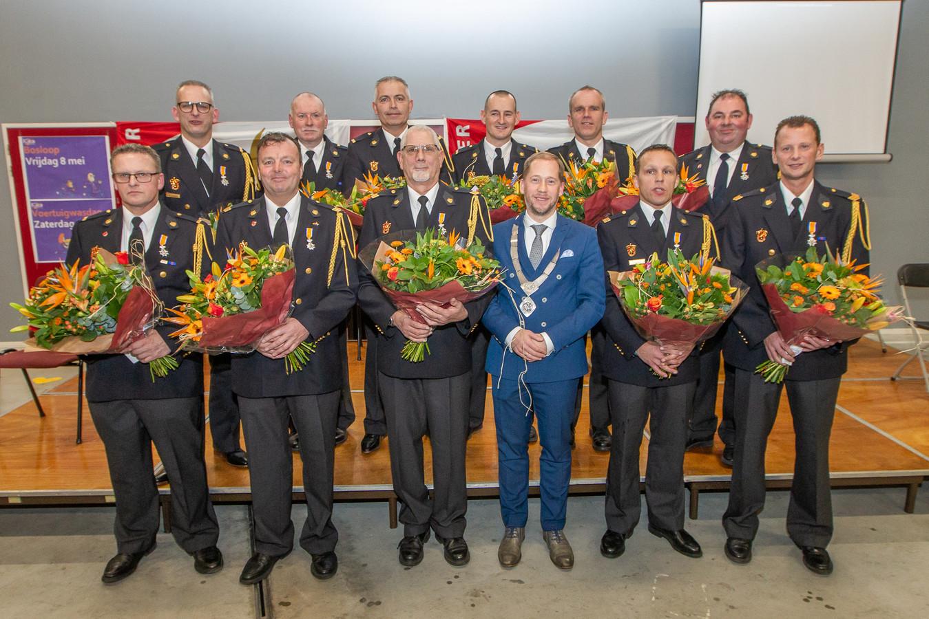 Burgemeester Jan Nathan Rozendaal van Elburg met de elf onderscheiden brandweerlieden.
