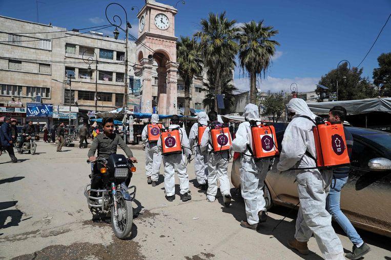 Leden van een Syrische ngo desinfecteren de straten van Idlib om verspreiding van het coronavirus te voorkomen.  Beeld AFP