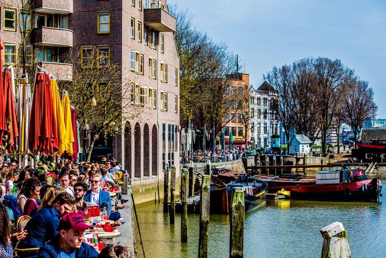 Mensen genieten van het mooie weer op het terras in de Oude Haven, Rotterdam. Beeld null