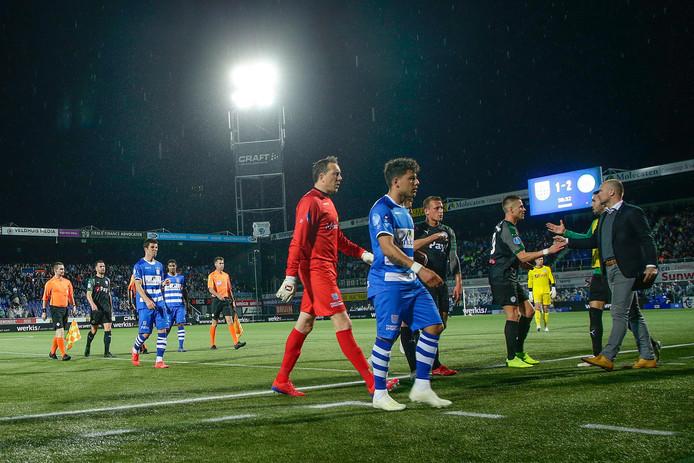 De spelers van PEC Zwolle en FC Groningen gaan vroegtijdig naar binnen. Vanwege onweer werd het duel woensdag ruim een half uur voor tijd gestaakt.