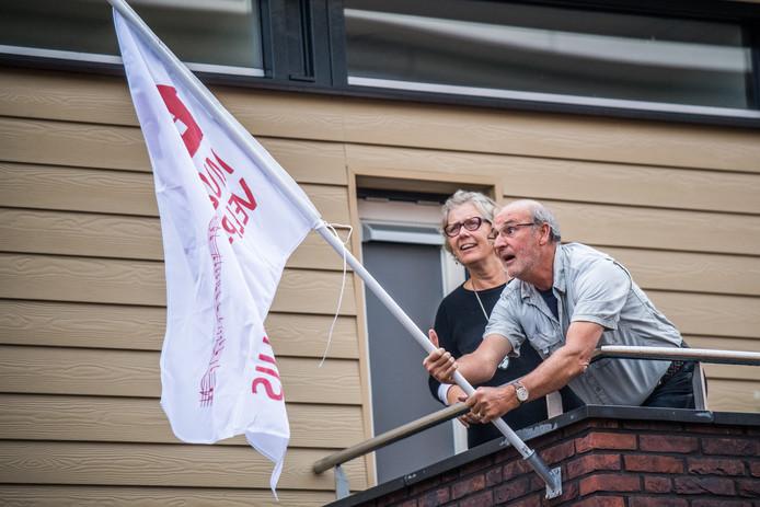 Werkgroepleden Dalien Prins Visser en Henny Kromhout van Muziek aan Huis bij de vlag van hun festival.