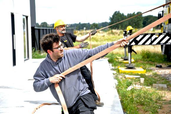 Nick helpt om de tweede container op het dak te plaatsen.