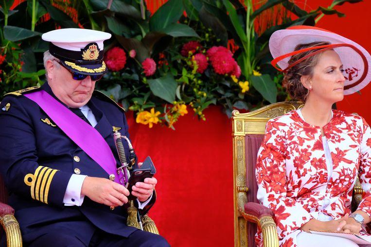 Prins Laurent bekommert zich even over zijn smartphone.
