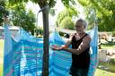 Camping Bij Ons in coronatijd. Wim Pesulima laat zijn zelfgemaakte, coronaproof douche onder een boom zien.
