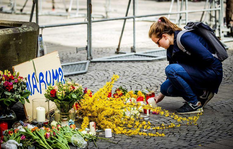 Een vrouw legt bloemen op de plek in het centrum van Münster, waar een busje inreed op een vol terras van het beroemde restaurant Grosser Kiepenkerl.