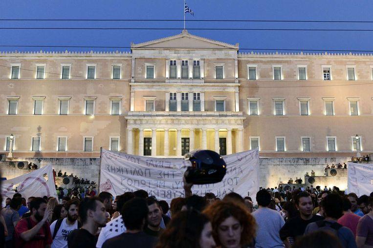 Grieken demonstreren tegen een akkoord met de eurolanden voor het Griekse parlement. Beeld afp