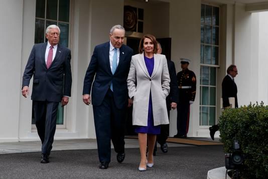 Chuck Schumer (midden) en Nancy Pelosi (rechts) verlaten het Witte Huis na weer een vruchteloos overleg.