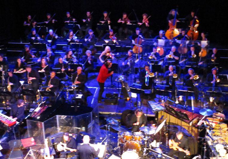 Rundgren, in rood jasje middden tussen het Metropole Orkest Beeld