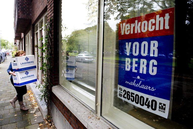 Een vrouw draagt verhuisdozen haar nieuwe huis in Rotterdam in. Beeld anp