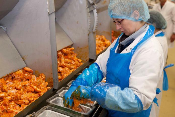 Een medewerker van Plukon verwerkt kip.