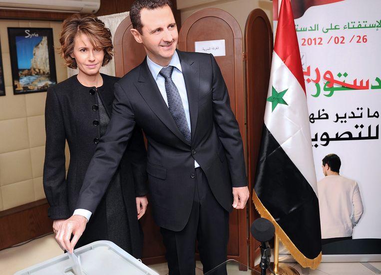 President Assad en zijn vrouw in het stemlokaal in Damascus waar ze hun stem voor het referendum over de grondwet uitbrengen. Beeld EPA