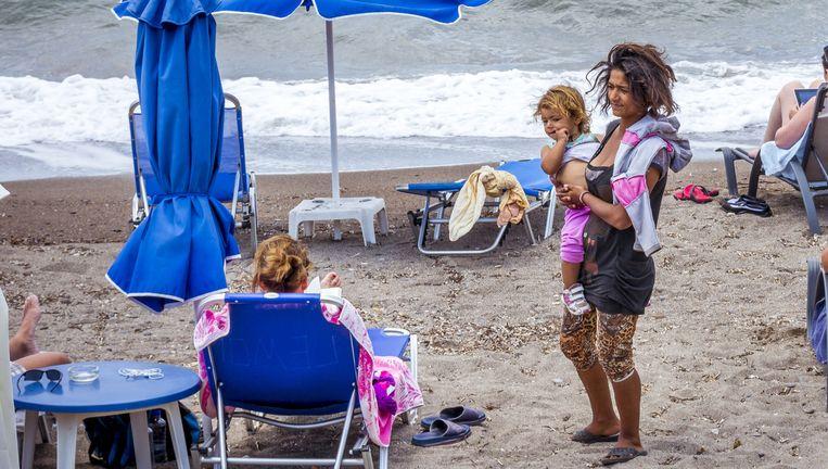 Een vluchteling bedelt op het strand van de Griekse badplaats Petra bij toeristen in de hoop wat geld te krijgen voor eten. Beeld anp