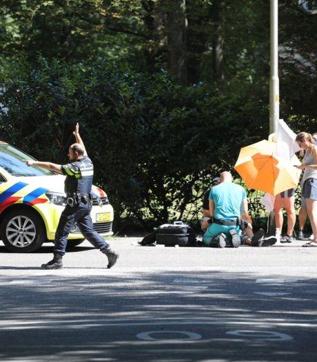 Omstanders houden geschepte fietser met paraplu's in de schaduw tot ambulance komt